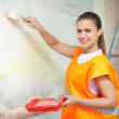 Smiling woman paints wall - Foto de Stock