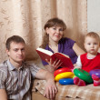 Family   with book at home — Stock Photo
