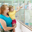 Mature woman with child at pharmacy - Stock Photo