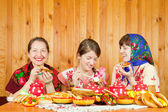Happy mother with daughters eating pancakes — Stock Photo