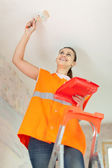 Female house painter paints the ceiling — Stock Photo