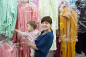 Happy woman and child chooses clothes — Stock Photo