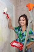 Happy girl paints wall with roller — Stock Photo