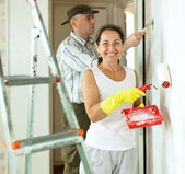 Smiling woman and man makes repairs — Stock Photo