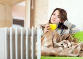 Vrouw in de buurt van olie verwarmer thuis — Stockfoto