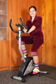 Woman working out on exercycle — Stock Photo