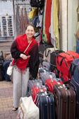 Mature woman chooses suitcase — Stock Photo