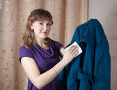 Woman cleaning coat — Stock Photo
