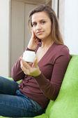 Woman puts cream on face — Stock Photo