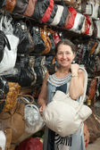 Woman chooses leather bag at shop — Zdjęcie stockowe