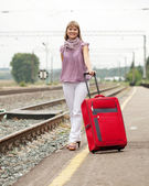 Woman with luggage on railroad — Stock Photo