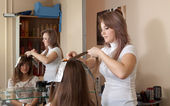 Stylist coloring long-haired girl hair — Stock Photo