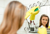 Woman cleaning mirror in bathroom — Stock Photo
