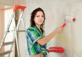 Woman paints wall — Stock Photo