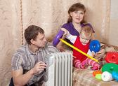 Family at home near oil heater — Stock Photo