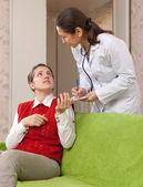 Läkaren frågar kvinnlig patient känns — Stockfoto