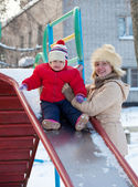 Mother with toddler on slide in winter — Stock Photo