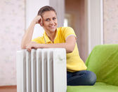 Happy woman near heater — Foto de Stock