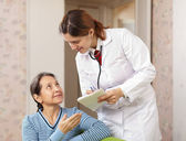 Friendly doctor asks mature patient feels — Stock Photo