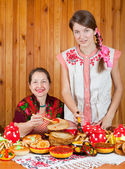 Mother with daughter eating pancake with caviare — Stock Photo
