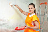 Smiling woman paints wall — Stock Photo
