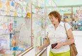Kobieta kupuje leki w aptece — Zdjęcie stockowe