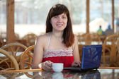 Woman with laptop at resort cafe — Stock Photo