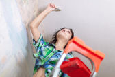 Girl paints ceiling at home — Stock Photo