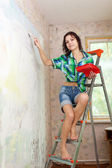 Girl paints wall at home — Stock Photo