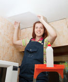 Woman glues ceiling tile — Stock Photo