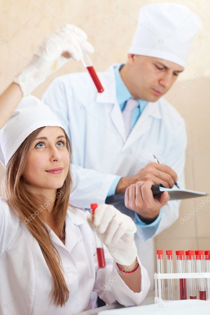 Male doctor and nurse with test tubes makes blood test in medical laboratory — Stock Photo #18200167