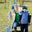 Woman and boy sits with spade - Foto Stock