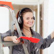 Woman in headphones paints wall — Stock Photo