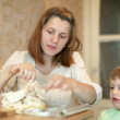 Woman with child cooking food — Stockfoto