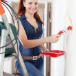 Stock Photo: Happy woman in overalls paints wall