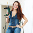 Young woman in overalls with drill — Stock Photo