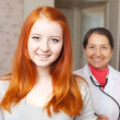 Happy healthy teenager against doctor - Stok fotoğraf
