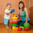 Happy mother and baby plays with toys — Stock Photo #23476469