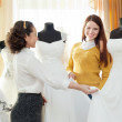 Shop consultant helps girl chooses white bridal outfit - Foto Stock