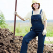 Female farmer works with manure - Stock Photo