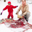 Mother with daughter cleans rug with snow — Stock Photo