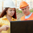 Foto Stock: Two architects works in front of building site