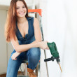 Happy girl with drill on stepladder — Stock Photo