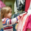 Baby girl chooses clothes at shop — Stock Photo