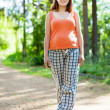 pregnant woman walks on  forest road — Stock Photo