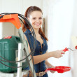 Happy woman in deniums paints wall — Stock Photo