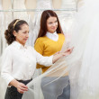 Shop assistant helps the bride in choosing bridal outfit — Stock Photo