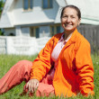 Happy mature woman in front of  home - Stock Photo