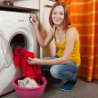 Foto Stock: Womputting clothes into washing machine