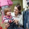 Stock Photo: Happy woman and child chooses jeans